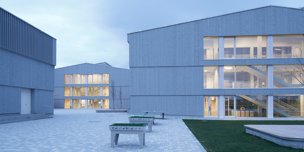 """Mit dem DGNB Preis """"Nachhaltiges Bauen 2016"""" prämiert: Das von Hermann Kaufmann Architekten und Florian Nagler entworfene Schmuttertal-Gymnasium in Diedorf ist ein aus vier Gebäuden bestehendes Ensemble, das sich, so die Jurybewertung, auf herausragende Weise in die Landschaft am Rand des Naturparks Augsburg einfügt. Der Einsatz hocheffizienter Haustechniksysteme und einer Photovoltaik-Anlage ermöglicht die Erzeugung von mehr Energie als verbraucht wird. Durch die Holzkonstruktion kommt zudem ein nachwachsender Baustoff zum Einsatz, der nur wenig graue Energie benötigt und eine gute CO2-Bilanz ermöglicht."""